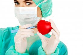 stock photo of scalpel  - Young female cardiologist surgeron holding heart and scalpel - JPG