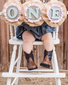 picture of cowgirl  - little cowgirl boots and a number one sign on a high chair - JPG
