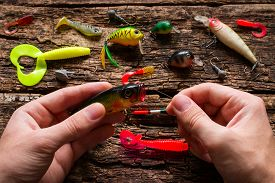 picture of fishing bobber  - man holding a fishing bait and fishing line - JPG