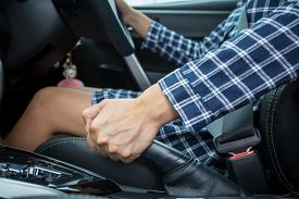 image of levers  - Closeup of young woman pulling handbrake lever in car - JPG