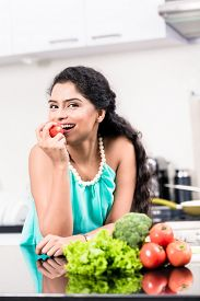 pic of indian apple  - Indian woman eating healthy apple in her kitchen - JPG