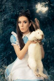 foto of bunny costume  - Portrait of a surprised girl in a blue costume holding a white bunny  - JPG