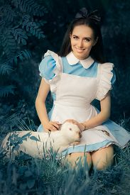 image of bunny costume  - Portrait of a smiling girl in a blue costume holding a white bunny - JPG