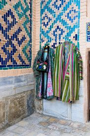 stock photo of samarqand  - Tourists can choose the traditional Uzbek clothes and acsessories in numerous stalls in the courtyard of Tilya Kori Madrasah Samarkand Uzbekistan - JPG