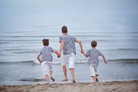 picture of squirt  - Three merry happy brother plays at sea laughing and squirting water italy - JPG
