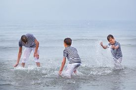 stock photo of squirt  - Three merry happy brother plays at sea laughing and squirting water italy - JPG
