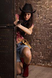stock photo of revolver  - A Girl cowboy shoots from a revolver - JPG