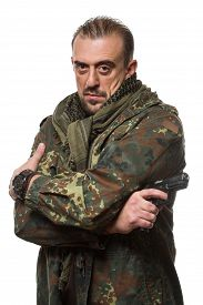 picture of terrorist  - Male terrorist in a military jacket with a gun in his hand - JPG