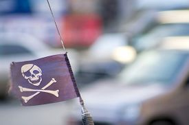 picture of skull crossbones flag  - Black pirate flag with skull and crossbones flying on the car antenna on the background of the traffic - JPG