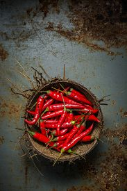 foto of red hot chilli peppers  - Red Hot Chili Peppers in coconut shell on rusty steel background - JPG