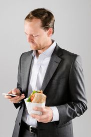 pic of annoying  - Annoyed businessman with take away lunch sandwich working on his phone texting a message - JPG