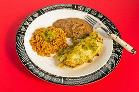 picture of enchiladas  - Chicken Enchilada Dinner spicy salsa verde on Aztec Design Plate with rice and beans against bright red background - JPG