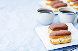 stock photo of eclairs  - eclairs with cheese cream and chocolate glaze on a blue background - JPG