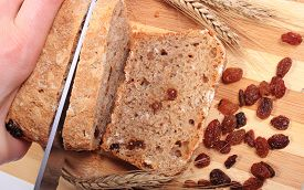 pic of fresh slice bread  - Slicing fresh baked wholemeal bread ears of wheat and heap of raisins lying on cutting board concept for healthy eating - JPG