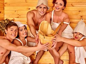 stock photo of sauna woman  - Group people in  hat  relaxing at sauna - JPG