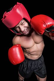 stock photo of headgear  - High angle view of boxer with headgear and gloves against black background - JPG