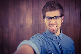 picture of sticking out tongue  - Portrait of hipster sticking out tongue against wooden wall - JPG