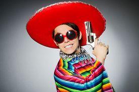 image of handgun  - Man in vivid mexican poncho holding handgun against gray - JPG