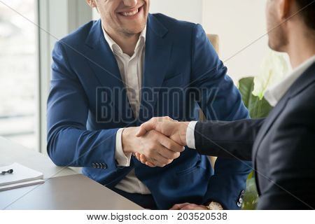 poster of Businessman in blue suit handshaking at business meeting, trying to make positive first impression on partner at negotiation, welcoming new colleague in office. Successful partnership, close up