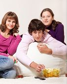 Friendly teens eating crisps and watching TV