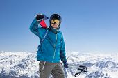 Happy smiling skier during active winter holidays. Man in winter clothing walking in snow and carryi poster