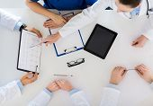 medicine, healthcare and cardiology concept - group of doctors with cardiogram, clipboard and tablet poster