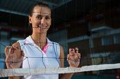 Portrait of smiling female volleyball player standing behind net at court poster