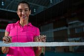 Portrait of smiling female volleyball player standing behind net poster