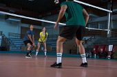 Full length of players practicing volleyball at court poster