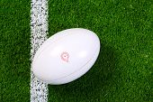 Photo of a rugby ball on a grass next to the white line, shot from above.