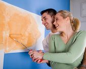 picture of married couple  - young married couple painting walls of their new home - JPG