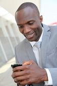 stock photo of mobile-phone  - Portrait of businessman using mobile phone - JPG