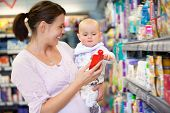 Cheerful mother playing with baby and spending time in shopping store