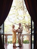 stock photo of waltzing  - senior caucasian couple on vacation dancing on terrace in hotel - JPG