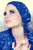beautiful woman in blue jacket and snow falling around her