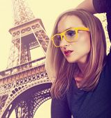 beautiful young blond woman wearing fashionable yellow glasses against Eiffel Tower in Paris with cr