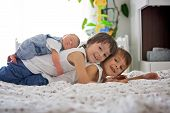 Постер, плакат: Two Children Toddler And His Big Brother Hugging And Kissing Their Newborn Baby Brother