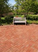 An Empty Wood Bench By A Brick Patio