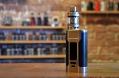 Electronic Cigarette On A Background Of Vape Shop. E-cigarette For Vaping. Popular Vape Devices poster