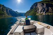 Woman driving a motor boat Seven Sisters waterfall on the background. Geiranger fjord, Beautiful Nat poster