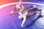 Two Young Sportsmens Wrestlers In Red And Blue Uniform Wrestling Against Wrestling Carpet, View Abov poster