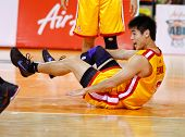 KUALA LUMPUR - FEBRUARY 19: Singapore Slingers Desmond Oh takes a tumble after a strong challenge at an ASEAN Basketball League match against Malaysian Dragons on February 19, 2012 in Kuala Lumpur.