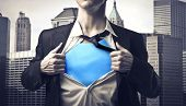 stock photo of undressing  - Closeup of a businessman showing the superhero suit under his shirt - JPG