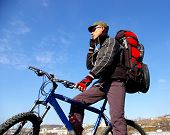 pic of sakhalin  - Man on bicycle with rucksack on background blue sky and peak of mountain - JPG