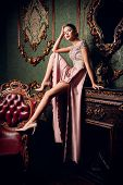 A full length portrait of a mysterious lady in a fluffy long dress posing in the interior. Interior, poster