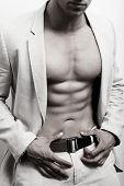 Hombre musculoso y sexy abs traje sobre pared blanca