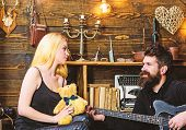 Man Play Guitar While Lady Holds Teddy Bear In Hands. Couple Spend Romantic Evening, Wooden Interior poster