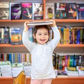 Cute Young Toddler Standing And Holding Book In Head. Little Happy Laughing Girl Indoors In Front Of poster