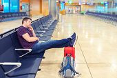 Tired Middle Aged Man Sleeping With Legs On Suitcase In Departure Hall. Tourist Sleeps Due To Delay  poster