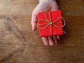 Red Paper Present Box & Golden Gift Ribbon In Hand On Wooden Background. Red Box For Surprise, Givin poster